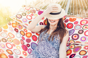happy beautiful hipster girl relaxing in hammock on the beach in summer evening light. joyful woman in straw hat resting and having fun in sun, summer vacation. space for text