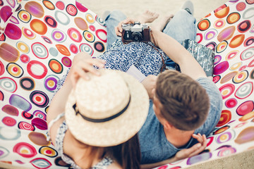 Adorable hipster couple taking selfies on a hammock near the beach, beautiful girl and handsome man taking selfie with old film camera while on vacation with books