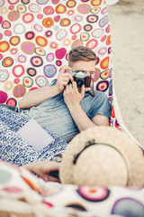 Handsome man taking picture of a beautiful brunette girl, hipster couple with old film camera making photographs on a hammock near a beach close-up