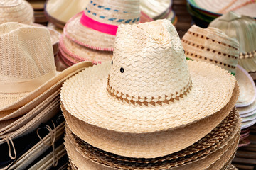 Many styles of hats made from natural materials.