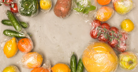 many different fruits and vegetables are wrapped in plastic foil, packed on concrete background
