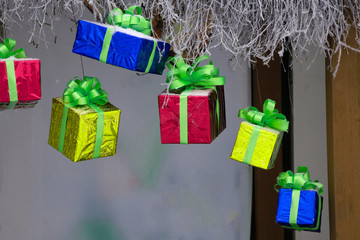 Red gift boxes hanging on a ribbon Old brown paper background