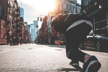 Athlete man in running start pose on urban street. Male runner preparing to run straight through Manhattan streets