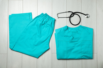 Clean scrubs and stethoscope on wooden background, top view. Medical objects