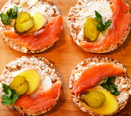 Sandwiches with cottage cheese, red fish, ginger and pickled cucumber on a cereal loaf