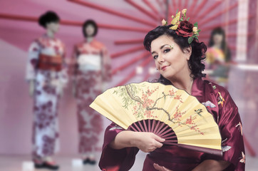 Caucasian woman dressed as a Japanese woman poses on kimono storefront blurred background in Asakusa neighborhood