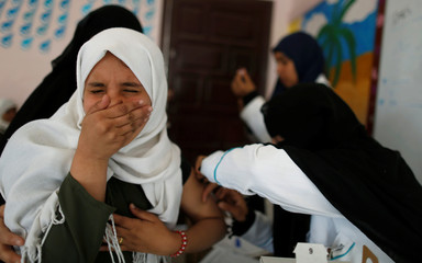 Girl reacts as she receives a vaccination for measles and rubella at her school as a six-day immunization campaign kicks off in Sanaa