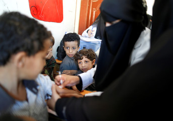 Boys look as another boy receives a vaccination for measles and rubella at their school as a six-day immunization campaign kicks off in Sanaa