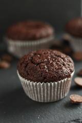Chocolate homemade cupcakes muffins on a black background with chocolate drops in the background. Bakery style. Dark food photo vertical