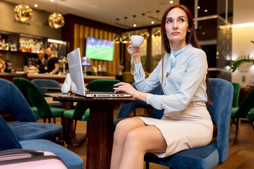 Pleasantly looking young woman with long ginger hair sitting in airport lounge, having tea and talking on mobile phone, leaving her country on business trip.