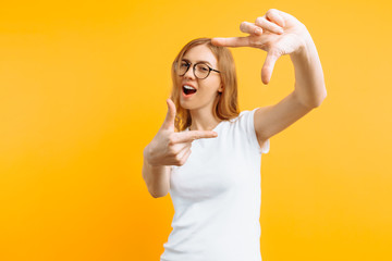 Beautiful young girl with glasses making a camera frame with fingers, on a yellow background