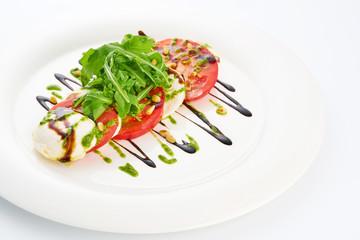 Mozarella cheese, tomatoes, arugula and pesto sauce in white plate.
