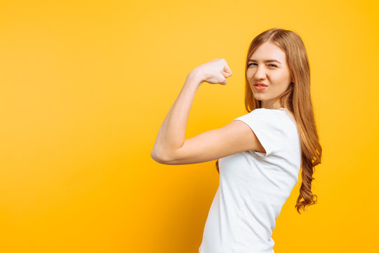 of happy girl in white t-shirt showing arm muscles on yellow background.