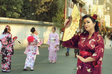 A caucasian woman dressed as a Japanese woman poses in Asakusa district