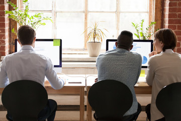 Diverse employees working together on computers in office, rear view