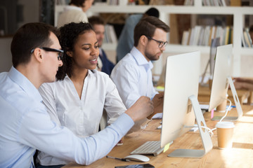 Diverse colleagues work together discuss online project pointing on computer