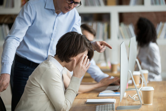 Stressed female employee suffering from discrimination of angry male boss