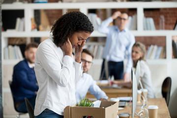 Sad african female employee packing belongings in box got fired