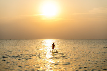 Stand up paddle board at sunset on the Phu Quoc beach Vietnam,travel concept,beach activity,Person stand up paddle boarding at dusk beautiful sunset colors