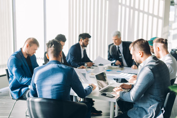 onstruction company management board members headed by grey-haired caucasian director analyzing company statistics during office meeting, consider stats diagrams making predictions