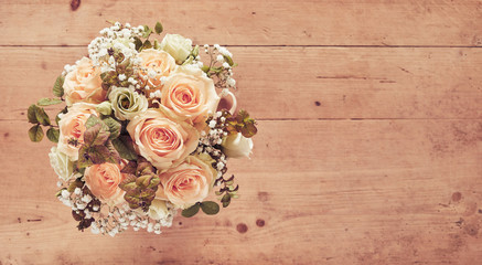 Wedding bouquet of pink roses on wooden background