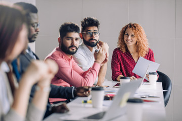 Mixed race diverse group of people in formal wear, sitting in raw at office table attending annual refresher course, led by a red-haired female coach