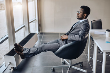 afro-american businessman resting after the conference in his room. full length side view photo. relaxation. free time. man is waiting for his companions