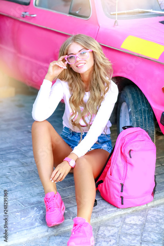 Stylish girl with denim jacket near the pink car with a pink