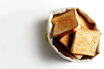 Fried toast bread slices in white bag. Copy space