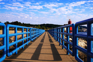 Pier with a bright blue fence in perspective. Big Red Lighthouse. Michigan, Ottawa County