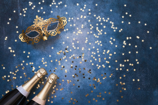 Two champagne bottles, golden carnival mask and confetti stars  on blue background. Christmas background, top view, copy space.