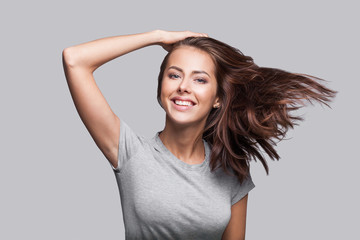 Pretty girl with long hair laughing and enjoying life. Beautiful joyful girl with long brown hair portrait. Isolated on gray background