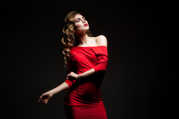 Dancing woman in red dress on black background