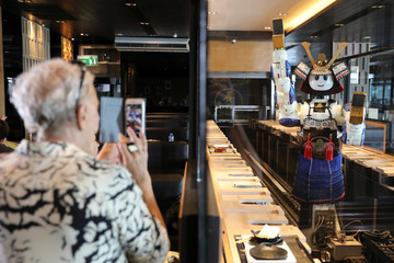 A robot waitress dances while a costumer takes a picture at the Hajime Robot restaurant in Bangkok