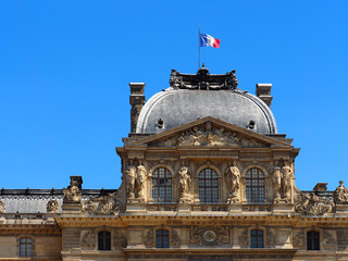 France flag on the roof of the Palais du Louvre. Sunlight day