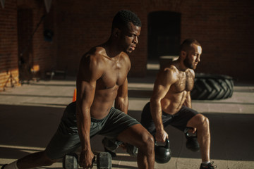 sport, crossfit lifestyle and people concept - two young caucasian and african male athletes with dumbbell making lunges with weight in indoor workout