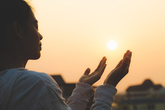 Woman praying in the morning on the sunrise background. Christianity concept. Pray background. Faith hope love concept.