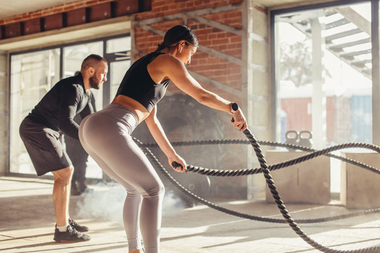 Caucasian fit couple exercising with battle ropes at gym. Woman and man dressed in sports outfit training together doing battling rope workout, with powder and dust particles flying in the sun rays
