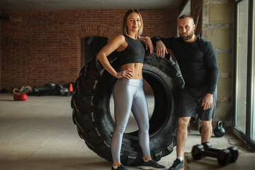 Healthy active couple of diverse caucasian sportspeople looking at camera while training in crossfit workout in gym. Sport and healthy lifestyle motivation.