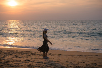 Happy young woman enjoying freedom walk on the beach and sea sky sunset background