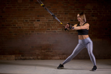 Crossfit female instructor doing full body TRX session workout in gym with red brick walls.