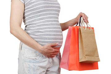 Pregnant woman with various clothes for a newborn