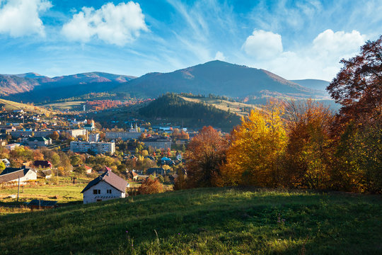 countryside beautiful autumn evening in mountains. small town in the distant valley. colorful trees on the hill. wonderful sunny weather with beautiful sky