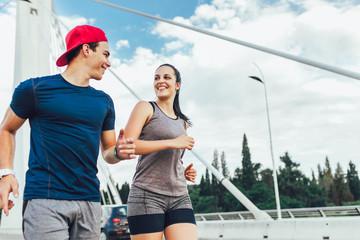Happy couple running across the bridge. Healthy lifestyle.