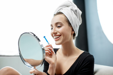 Woman whitening teeth with gel at home