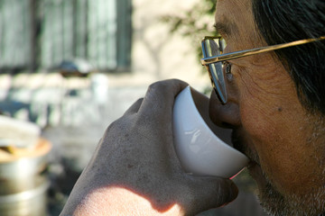 A man drinking a warm cup of Japanese tea on a cold morning
