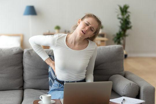 Young tired woman feeling pain in spine massaging back