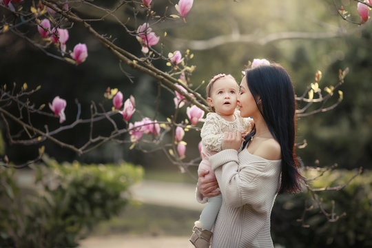 Young mother and little daughter in autumn park play with magnolia leaves. Happy weekend with family in autumnal forest park. People in park. Smiling woman and baby in outdoor. Fall. Sunny day