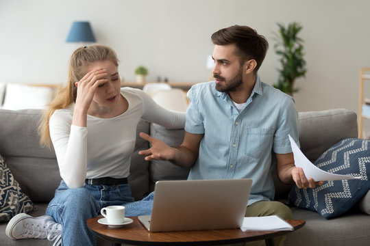 Stressed unhappy couple arguing about expenses with laptop and papers