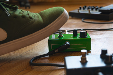 guitarist foot on guitar effect pedal in a studio